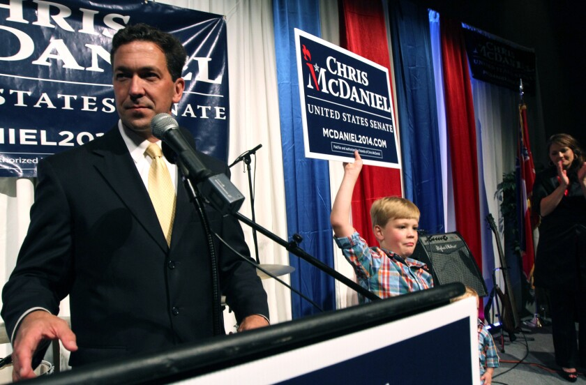 Chris McDaniel addresses his supporters as his son Cambridge, 7, joins him on the stage at the Lake Terrace Convention Center in Hattiesburg, Miss.