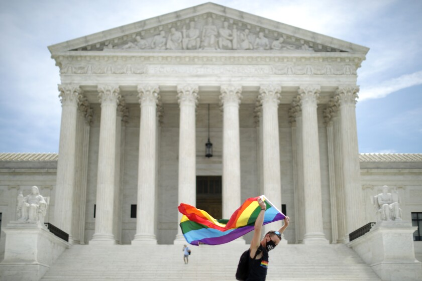 Holding a Pride Flag, Joseph Fons walks in front of the U.S. Supreme Court building in June.