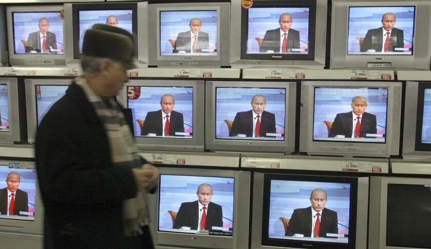 A man walks past a display with TV-sets, showing the annual press conference of Russian President Vl