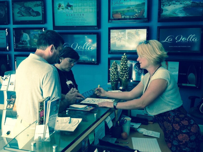 Heather Vrana, a fulltime employee in the LJVMA's Information Center at  1162 Prospect St., helps Delsa and Joseph Charbonnet of Slidell, Louisiana, find fun things to do in the Village via a tourist map provided at the center (the couple was in La Jolla for their son's wedding). Moving forward, Vr