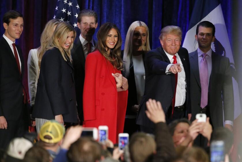 El empresario Donald Trump, aspirante a la candidatura republicana a la presidencia, señala a un seguidor mientras se marcha con su familia de su mitin en la noche de primarias. (AP Foto/Kiichiro Sato)