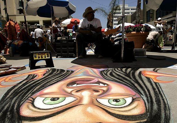 "Kevin Ramirez, a professional artist, with his chalk mural, ""Cuteness Can Gag a Vampire"" during the 18th annual Pasadena Chalk Festival in Pasadena. This is his eighth year participating. See full story"
