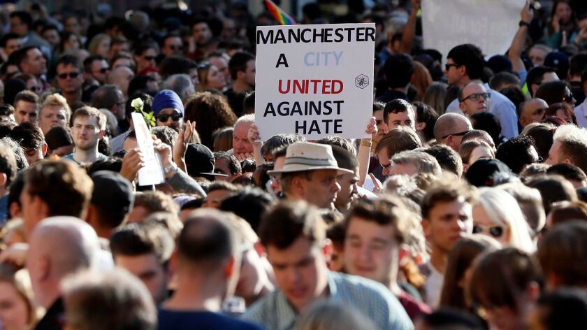 People attend a vigil in Albert Square, Manchester, England, Tuesday May 23, 2017, the day after the
