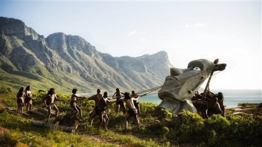 """In this undated image released by A+E Networks, Easter islanders erect the statue of Moai on the cliff in a scene from the History's 12-hour miniseries, """"Mankind the Story of All of Us,"""" airing later this year. The new series starts with the Big Bang and traces the development of humans, tools and the construction of the pyramids. (AP Photo/A+E Networks, Joe Alblas)"""