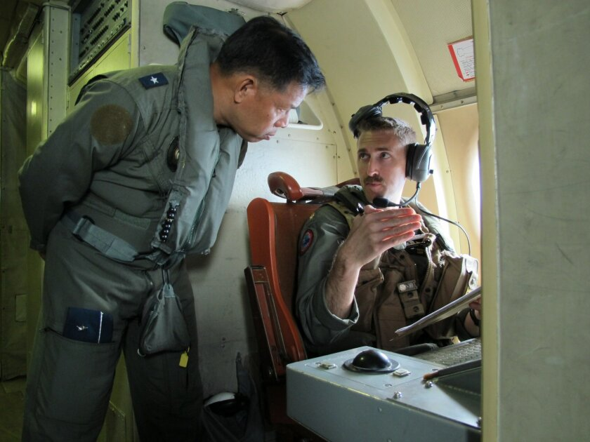 In this photo taken Thursday, June 25, 2015, Western Command deputy commander Brigadier General Guillermo Molina Jr. talks to U.S. Navy officer Patrick Ronan on board a P3 Orion plane during  the joint US-Philippines naval exercise dubbed CARAT (Cooperation Afloat Readiness and Training) 2015 over