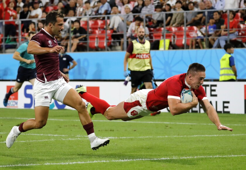 Wales Josh Adams dives across the line to score his side's third try during the Rugby World Cup Pool D game between Wales and Georgia at Toyota City Stadium, Toyota City, Japan, Monday, Sept. 23, 2019. (AP Photo/Christophe Ena)