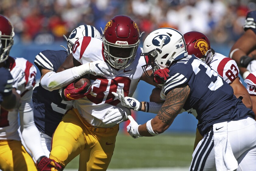 USC running back Markese Stepp tries to push past BYU linebackers Jackson Kaufusi, right, and Max Tooley during the first half.