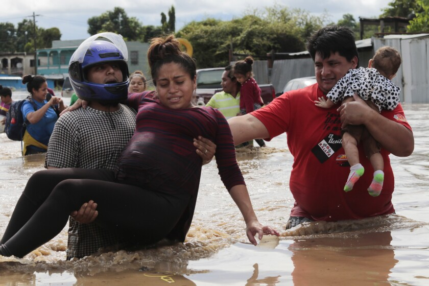 A pregnant woman is carried out of an area flooded by Hurricane Eta in Honduras, earlier this month.