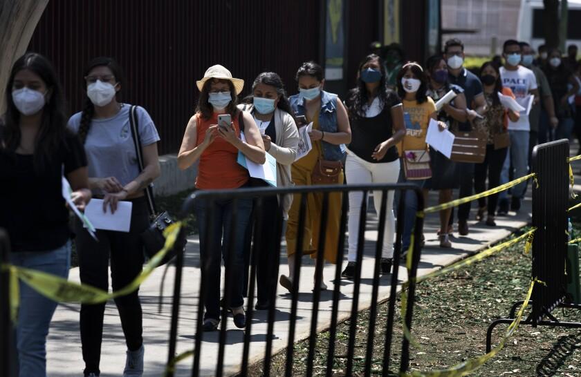 Educadoras hacen fila para que les pongan la vacuna de CanSino contra el COVID-19