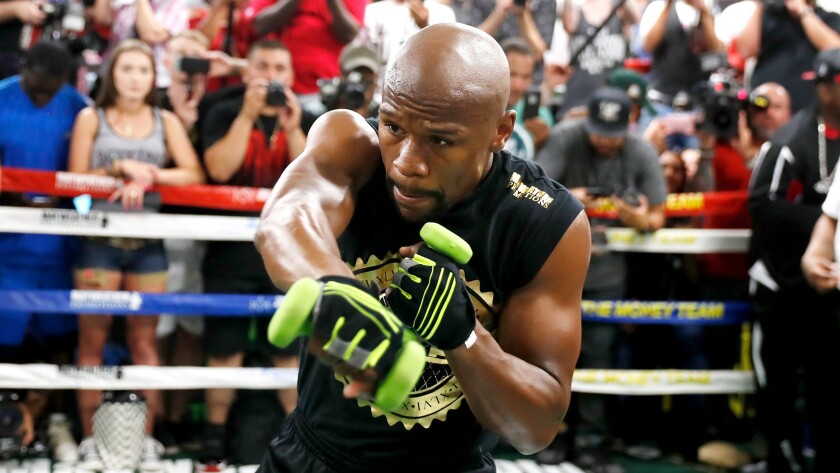 Floyd Mayweather Jr. shadow boxes with weights in his hands during a workout open to the media on Aug. 10 in Las Vegas. Mayweather has used a perfect combination of skill and charisma to make himself one of the highest paid athletes in history.
