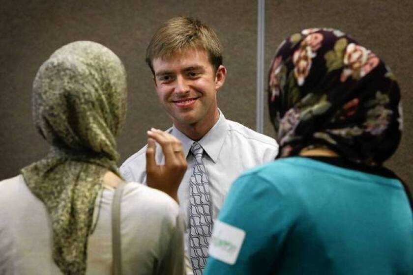 "Mormon student Chase Davis and Muslim students Afra Khan, left and Ambreen Baig discuss their religious beliefs during a ""speedfaithing"" session."