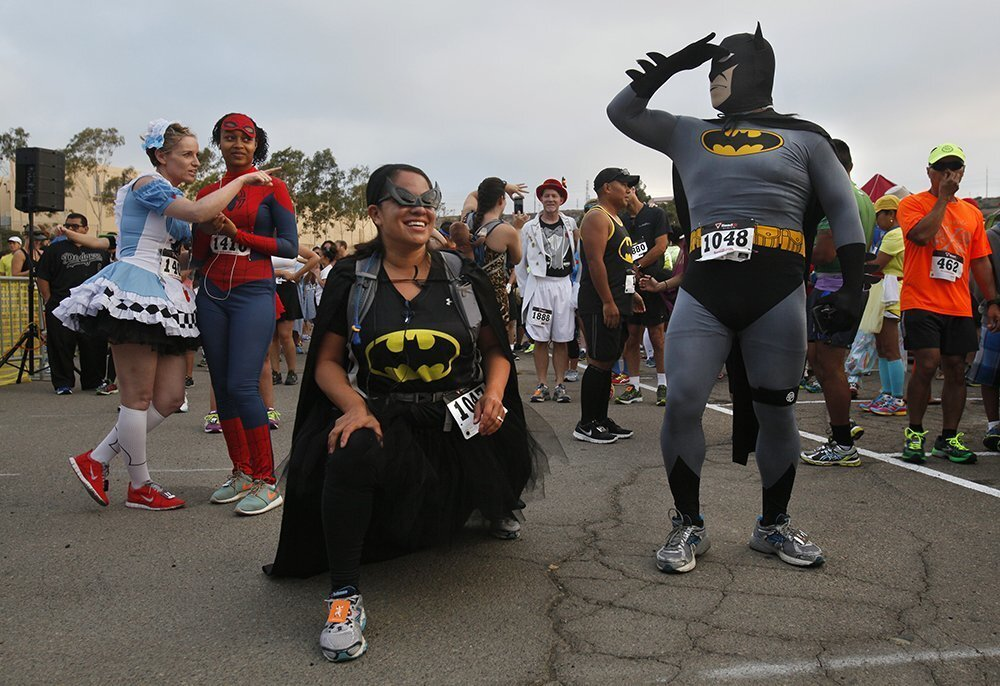 Sister and brother team Regina Isaias, as the Catwoman, and Ezequiel Paredes, as Batman, stretch before running Sunday morning in the second annual Costume Party Run to benefit San Diego's Boys and Girls' Clubs.