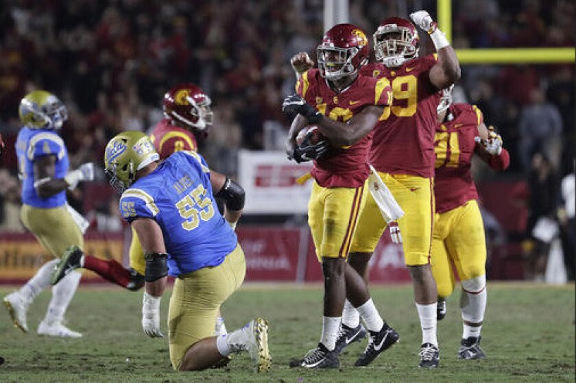 USC linebacker John Houston Jr. celebrates after scooping up a Josh Rosen fumble during second quarter action at the Coliseum.