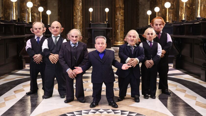 Warwick Davis, center, is joined by goblins at the reveal of the Gringotts Wizarding Bank on the Warner Bros. studio tour.