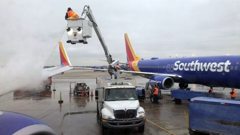 A Southwest Airlines plane is de-iced on Dec. 21, 2018 at Midway Airport. The airline said the partial government shutdown is grounding some government and contractor travelers and delaying some new service.