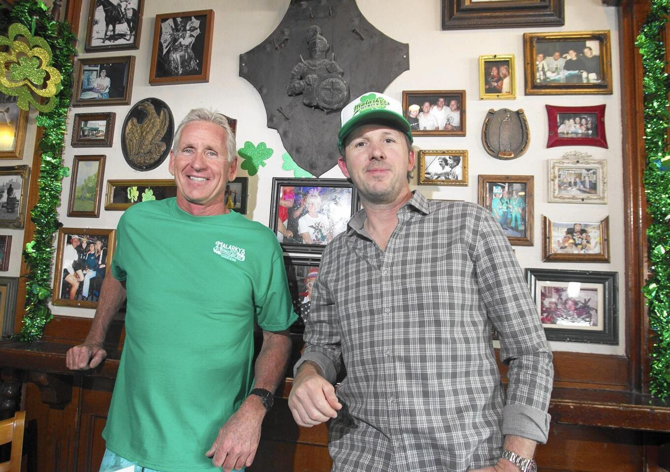 """Malarky's Irish Pub co-owners Brent Ranek, left, and Mario Marovic stand in front of the """"wall of fame"""" picture wall at the Newport Beach restaurant and bar, which is celebrating its 40th anniversary."""