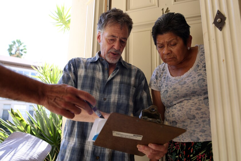 Jon Hofferman talks to fellow tenant Felicita Fuentes, right, with tenant Darrin Wilstead holding a pen at left, about their concerns with a proposed agreement with the owner of their apartment complex in Hollywood.