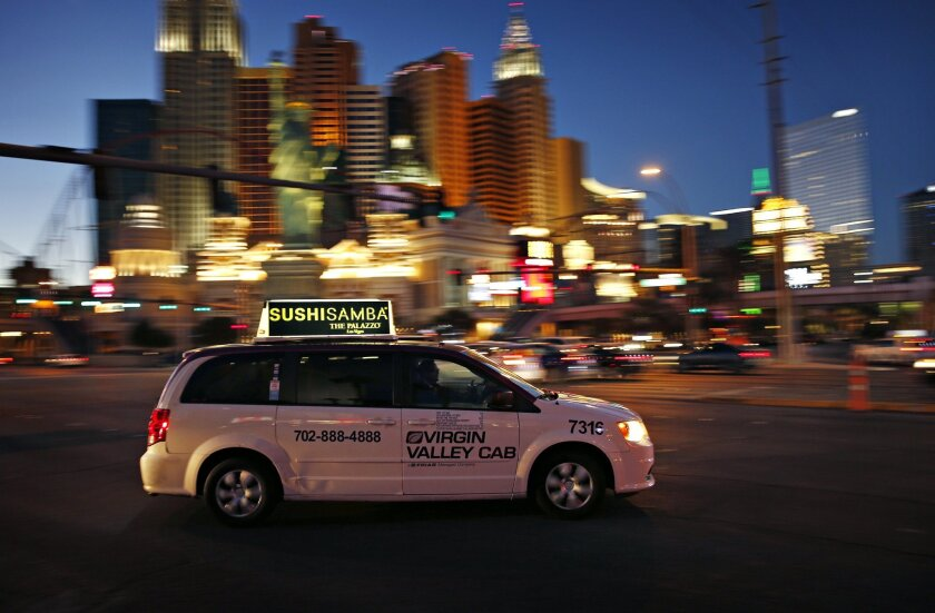 In this Feb. 9, 2016, photo, a taxi drives along Las Vegas Boulevard in Las Vegas. The advent of Uber and Lyft in Nevada last fall has thrown the powerful Las Vegas taxi industry and its regulators into upheaval, as the taxi industry's $3-per-ride credit card processing fee and lack of an online re