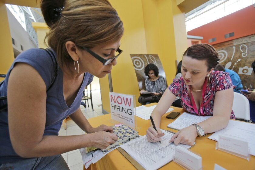 FILE - In this  Oct. 6, 2015 photo, A'GACI clothing store hiring manager Marcie Lowe, right, gives her card to job applicant Xionara Garcia, left, of Miami, during a job fair at Dolphin Mall in Miami. According to Labor Department statistics released Thursday, Nov. 5, 2015, more Americans applied f