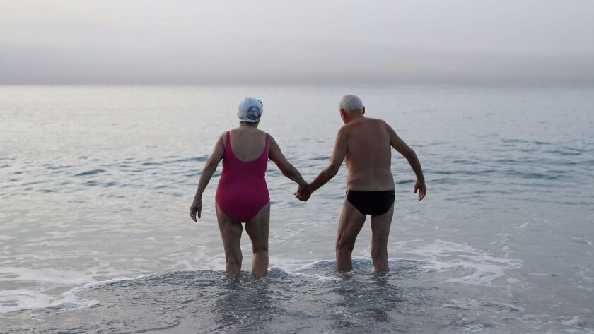View from behind of two senior citizens, a woman in a swim cap and pink swimsuit and a man in black swim briefs, stand in the ocean, holding hands.