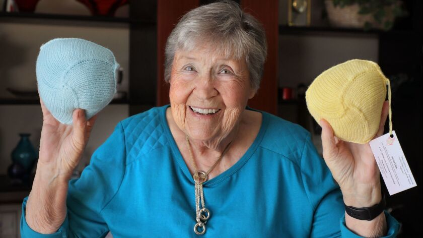 """Pat Anderson, 86, of Escondido holds two of her """"Busters"""" wardrobe accessories she knitted for breast cancer survivors who've had mastectomies."""