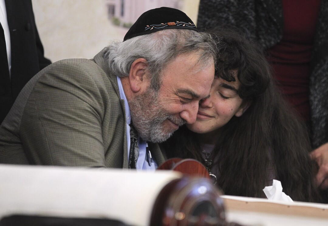 Howard Kaye, center, and his daughter Hannah Kaye hug after the final letter was inked into the new torah that's dedicated to wife and mother Lori Gilbert-Kaye, who was killed when a gunman attacked last April, during a celebration for the new torah at Chabad of Poway on Wednesday, May 22, 2019 in Poway, California.