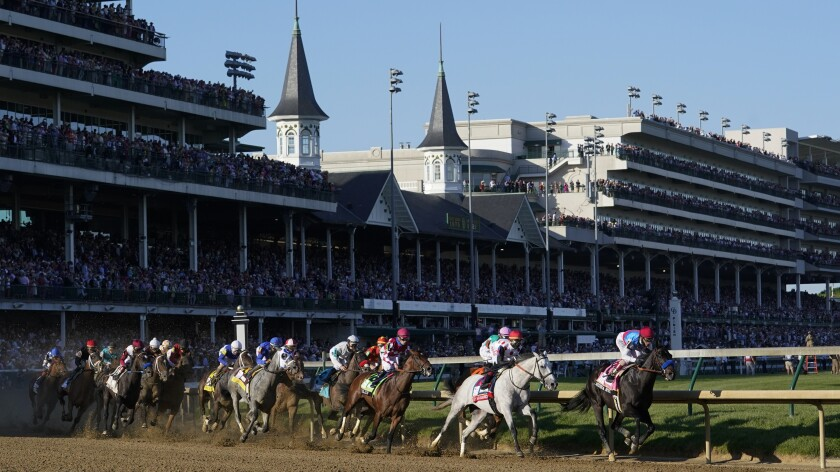 Horses and their jockeys race around a track.
