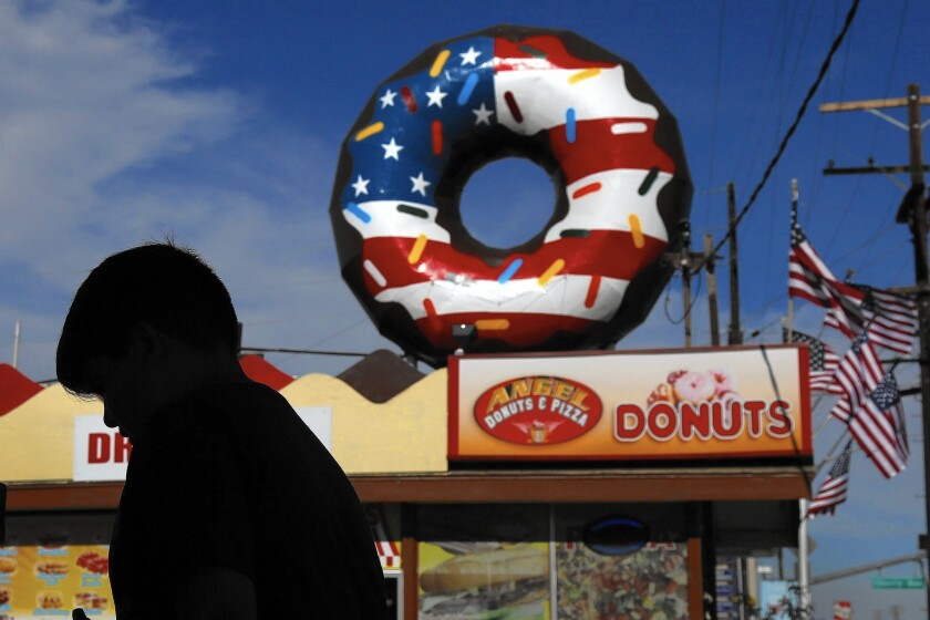 A patriotic design is iced across the doughnut-shaped sign at Angel Donuts and Pizza in Long Beach.