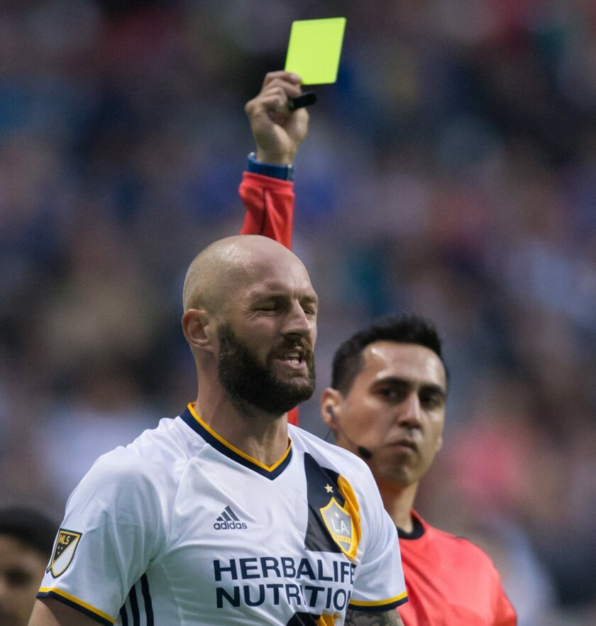 Los Angeles Galaxy's Jelle van Damme receives a yellow card from referee Jair Marrufo during the first half of an MLS soccer game against the Vancouver Whitecaps on Saturday, April 2, 2016, in Vancouver, British Columbia. (Darryl Dyck/The Canadian Press via AP)
