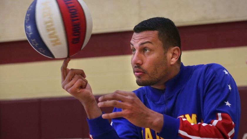Orlando El Gato Menendez, one of the famed Harlem Globetrotters, paid a visit to The Bishops School in La Jolla on Monday, taught a few people how to spin the ball on one fingernail.