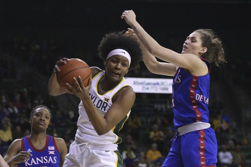 Baylor forward NaLyssa Smith (1) rebounds the ball against Kansas forward Mariane De Carvalho (4) in the first half of an NCAA college basketball game Wednesday, Feb. 5, 2020, in Waco, Texas. (AP Photo/Jerry Larson)