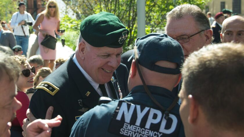 Lt. Gen. John F. Mulholland, Jr., former Task Force Dagger commander, shakes hands with a member of the New York City Police Department at Liberty Park during a ceremony for the America's Response Monument, which honored Special Force horse soldiers who fought in Afghanistan.