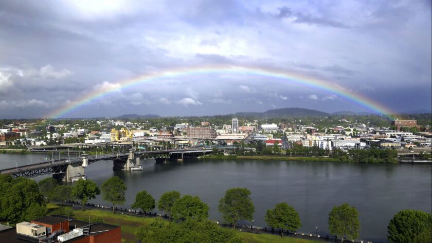 A rainbow pops out under dark rain clouds over the Willamette River in downtown Portland, Ore., Thur