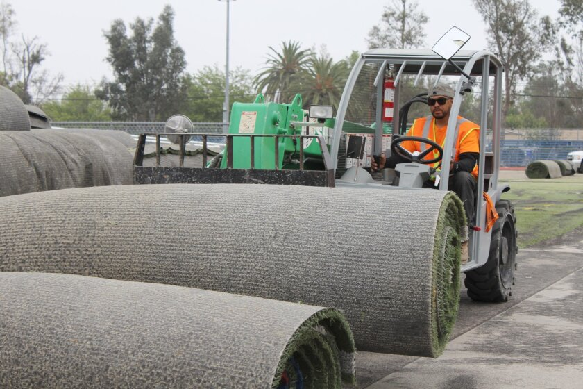 Steven Blanco with FieldTurf USA moves another roll of 10-year-old synthetic turf outside the Ramona High School field as workers prepare to lay new turf. The $500,000 project started last Thursday, and Ed Anderson, Ramona Unified's maintenance and operations supervisor, anticipates it will be comp