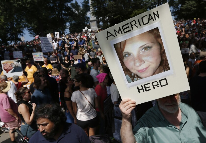 A counterprotester holds a photo of Heather Heyer during a rally in Massachusetts.
