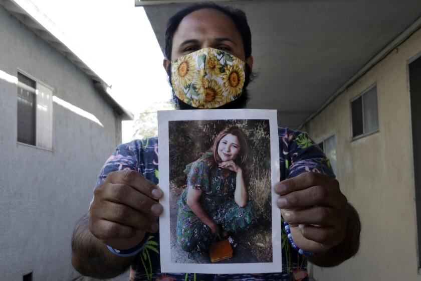 Albert Corado sostiene una foto de su hermana Melyda, quien fue asesinada a tiros por un oficial del LAPD