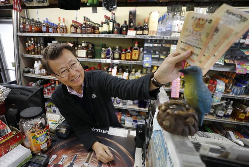 HAWTHORNE, CA - MARCH 27, 2019 James Kim, owner of Bluebird Liquor in Hawthorne rubs lottery ticke