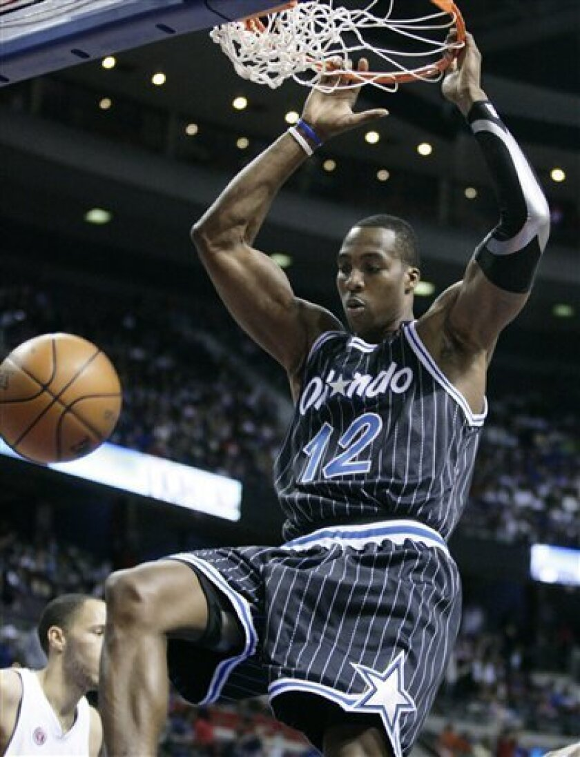 Orlando Magic center Dwight Howard dunks against the Detroit Pistons in the first half of an NBA basketball game Sunday, Jan. 31, 2010, in Auburn Hills, Mich. (AP Photo/Duane Burleson)