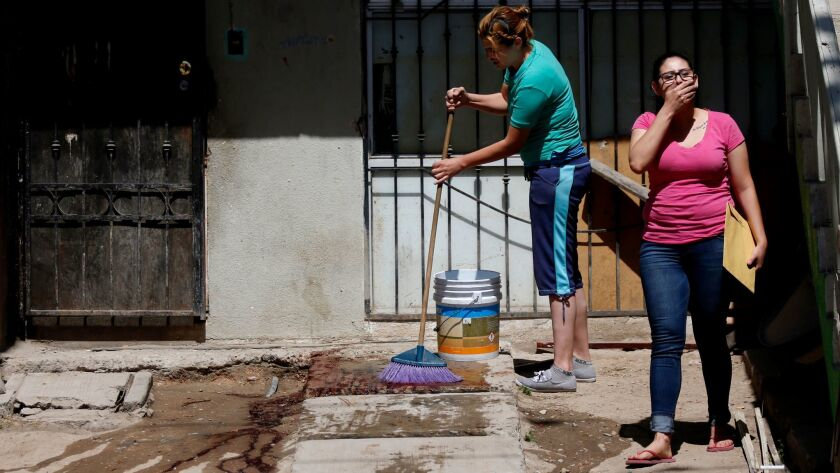 A Tijuana woman washes blood from in front of her house, where her husband was shot and killed in br