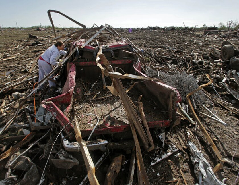 Sheila Slay looks into the cab of her pickup truck, which was thrown more than a quarter of a mile by the tornado that roared through Moore, Okla.