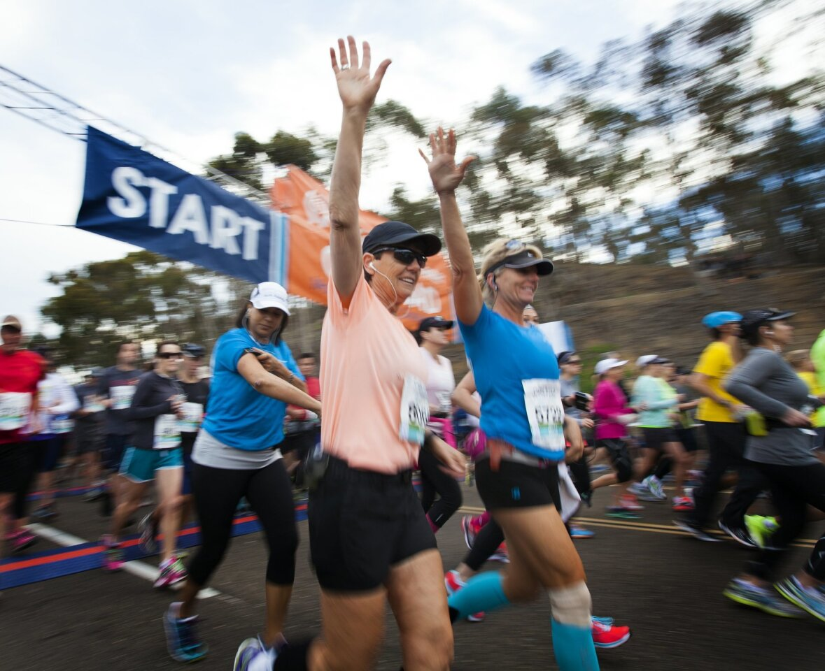 Diane Chappell and Kim Harvey raise their hands in excitement as they begin their run. Several thousand runners gathered Sunday morning for the 2015 Carlsbad Marathon.