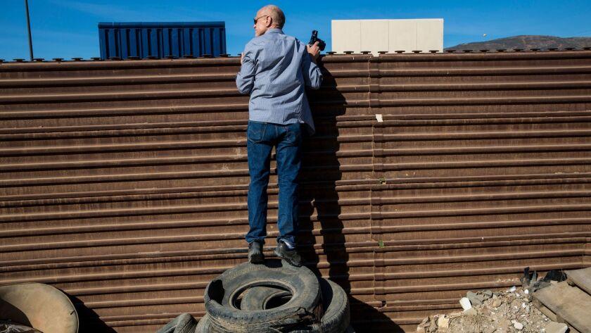TIJUANA, B.C., MEX - FEBRUARY 01: John Thurston peers over the border fence while standing atop tire