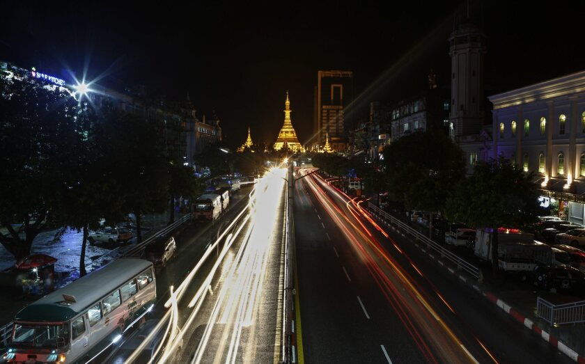 Traffic zooms through central Yangon, Myanmar, with the Sule pagoda in the background.