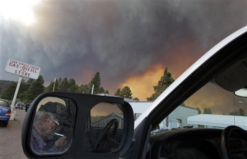 73-year-old Jerry Kinney, reflected in the mirror, lights a cigarette as smoke plumes from the Wallow fire fill the sky in Luna, N.M., Monday, June 6, 2011. Firefighters worked furiously Monday to save a line of mountain communities in eastern Arizona from a gigantic blaze that has forced thousands of people from their homes and cast a smoky haze over states as far away as Iowa. (AP Photo/Jae C. Hong)