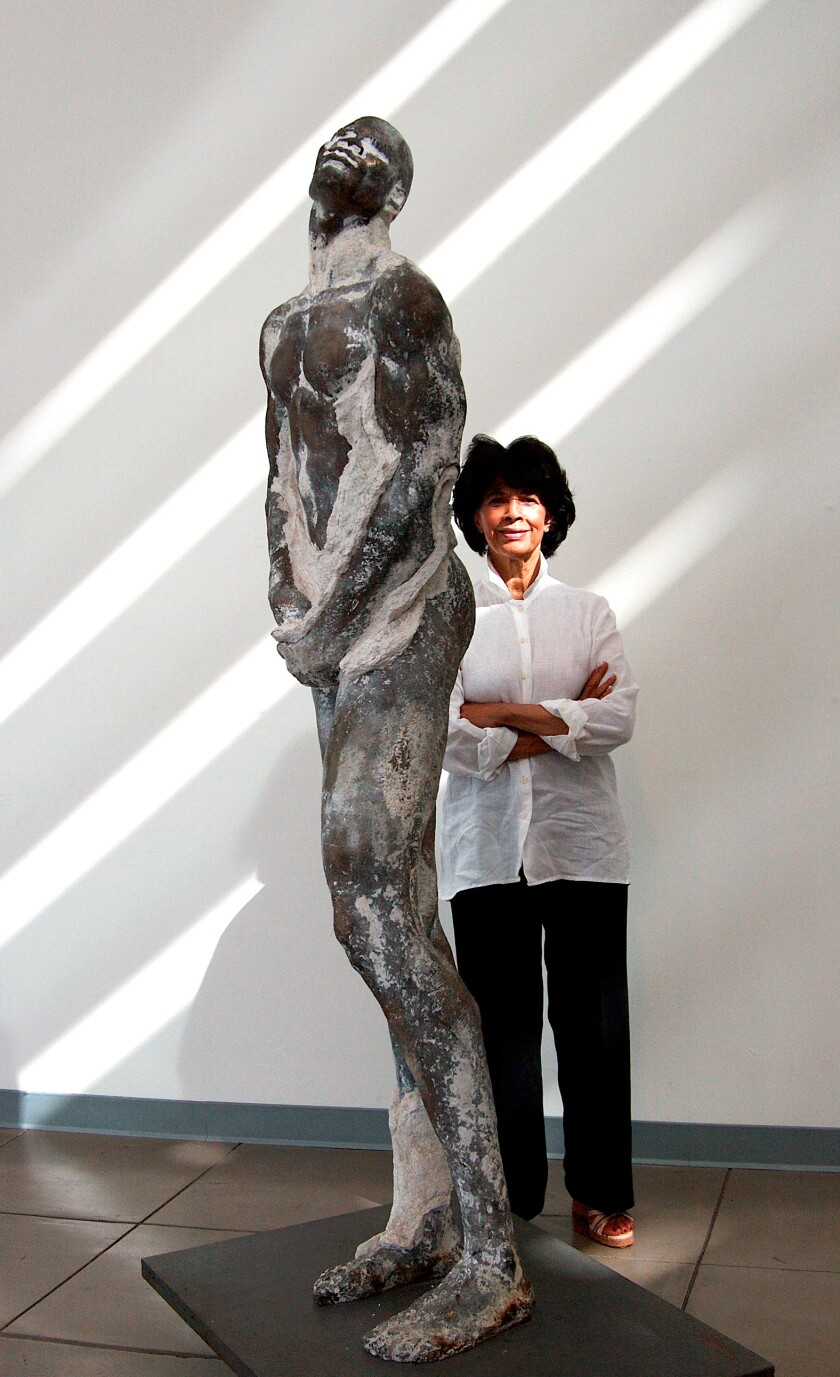 A woman in a white shirt next to a tall sculpture of a man