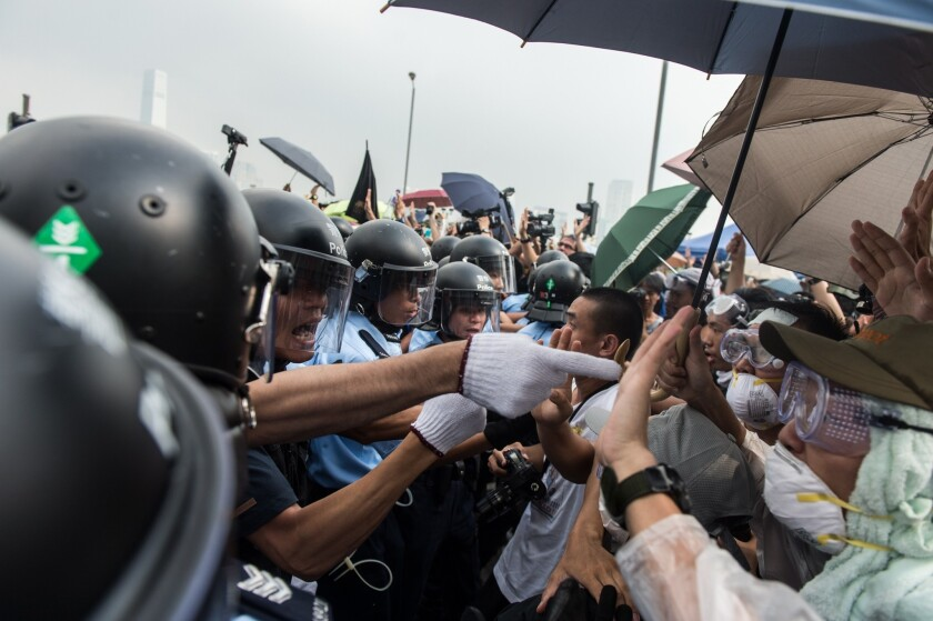 Police form a line to make way for an ambulance as pro-democracy protesters shout slogans outside the government headquarters in Hong Kong on Oct. 3.