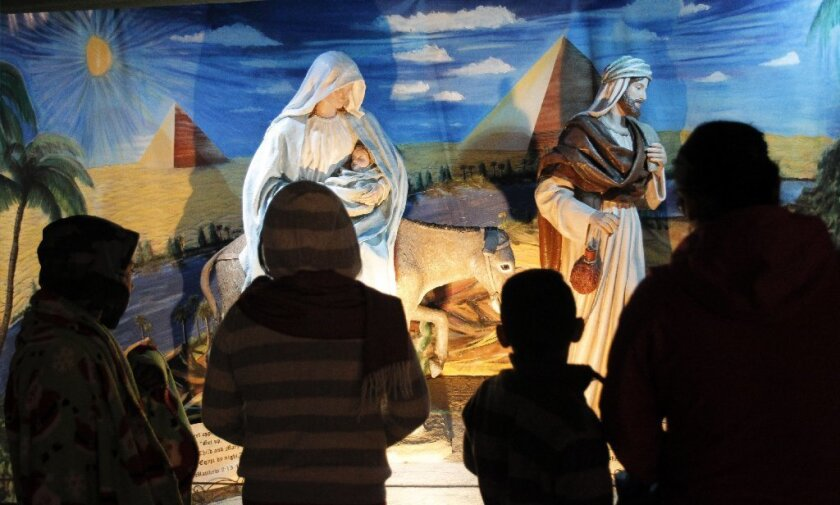 People look at the restored Nativity display during December Nights at Balboa Park in San Diego.