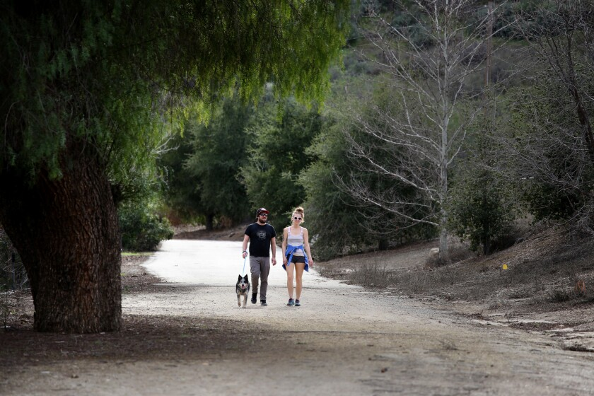 Mentryville, site of Southern California's first commercial oil well, is now a park. Marco Negovschi, Julia Hause and Roo the dog walk the Pico Canyon trail into the park.