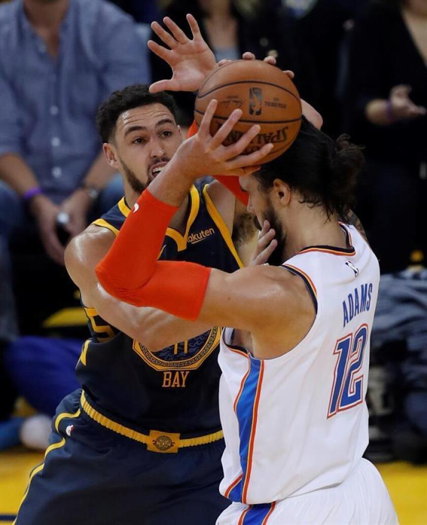 El pívot de los Thunder de Oklahoma Steven Adams (d) lucha por el balón con el base de los Warriors de Golden State Klay Thompson (i) durante el partido de la NBA que enfrentó a los Thunder de Oklahoma y a los Warriors de Golden Gate en el Oracle Arena en Oakland, California. EFE
