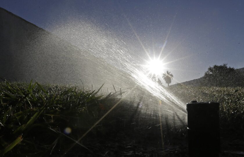 FILE - In this June 23, 2015, file photo a lawn is irrigated in Sacramento, Calif. A report is due out Thursday, Aug. 27, 2015 on monthly state water conservation figures. Many California cities are conserving well, and officials are turning their attention to the few cities/agencies that aren't do